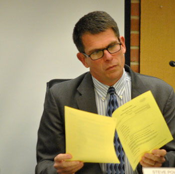 Ann Arbor city administrator Steve Powers peruses the printed copy of the council's agenda.