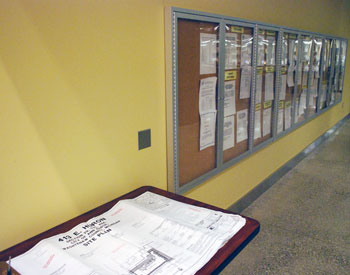 Plans under review sit on a table in the Ann Arbor city hall lobby, next to the glass cases that hold public notices.