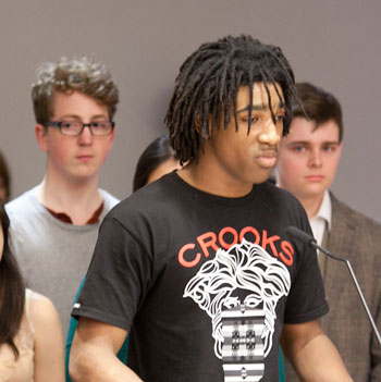 Sena Adjei, surrounded by other high school theater members, spoke against cuts to the theater program
