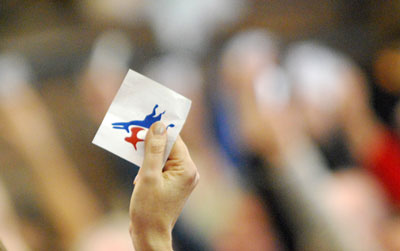 Attendees held their credential aloft to vote.
