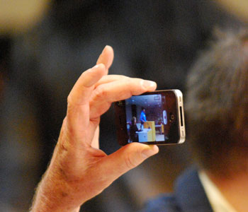 The proceedings were documented by several people in the audience using smartphones.